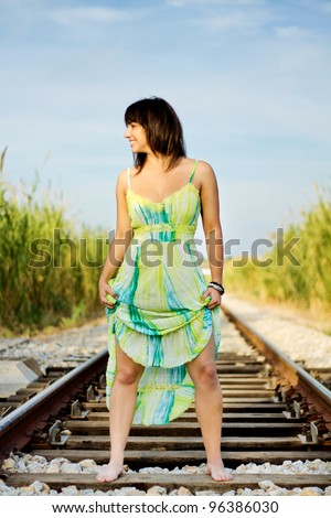 View of a beautiful girl with a spring dress on a railway.