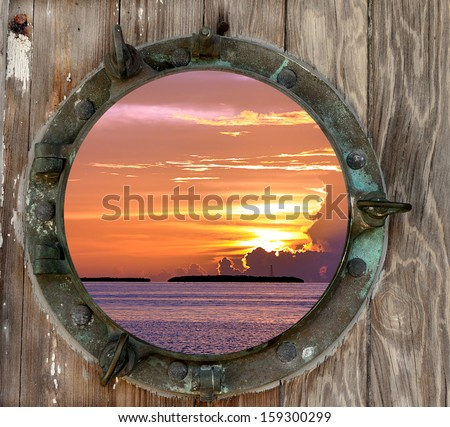 View of a beautiful Key West, Florida sunset, as seen through a old rustic porthole. - stock photo