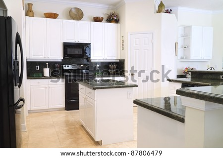 View of a beautiful modern kitchen with upscale appliances, white cabinets, and green granite countertops - stock photo