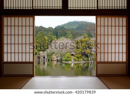 View of a beautiful oriental pond seen through open Japanese sliding doors - stock photo