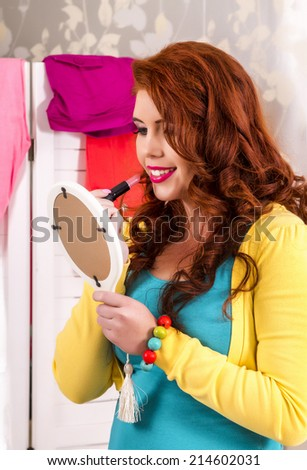 View of a beautiful redhead girl in her colorful bedroom, applying lipstick. - stock photo
