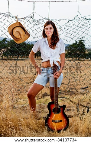 View of a beautiful young country girl with a guitar on the fence of the grassland.
