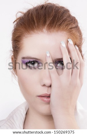 View of a beautiful young natural red hair woman with hand on face.