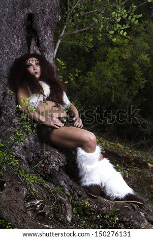 View of a beautiful young strong hunter warrior woman next to a tree.