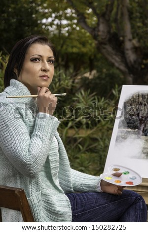 View of a beautiful young woman painting on a urban park. - stock photo