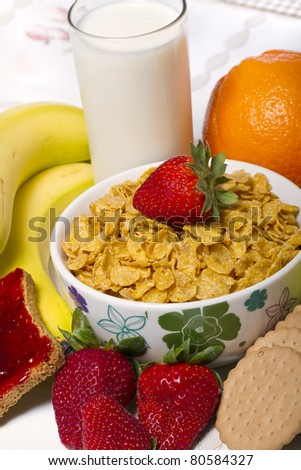 View of a bowl of cereals surrounded by fruit and milk. - stock photo