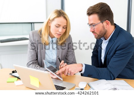 View of a Businessman and his assistant working together at the office - stock photo