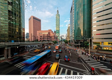 View of a busy street corner at rush hour in Downtown of Taipei City with cars and buses dashing by, Taipei 101 Tower and World Trade Center Buildings in Xinyi District and people passing on crosswalk - stock photo