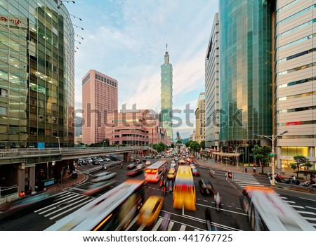 View of a busy street corner at rush hour in Taipei, the capital city of Taiwan, with cars and buses dashing through the intersection, Taipei 101 Tower & World Trade Center in Xinyi District Downtown