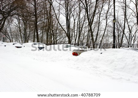 View of a city street with cars covered in snow during the winter season storm blizzard - stock photo