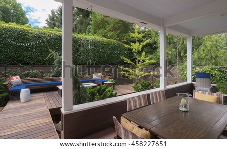 View of a contemporary conversation bench on a wooded deck as seen from a porch.