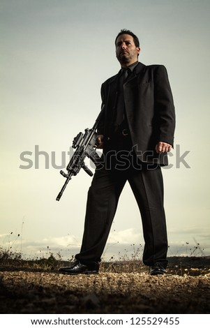 View of a contracted type killer agent wandering with a jacket and machine gun. - stock photo