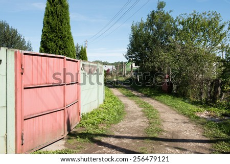 View of a countryside mud road with houses on both sides on a sunny morning.  - stock photo