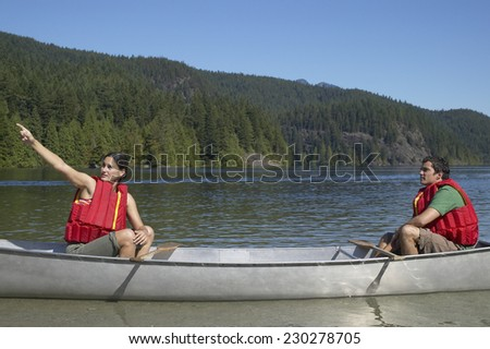 View of a couple canoeing and pointing into the distance - stock photo