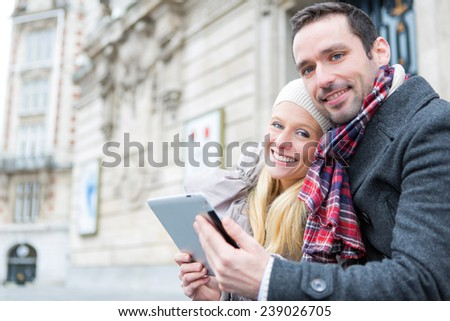 View of a Couple of young attractive tourist watching tablet