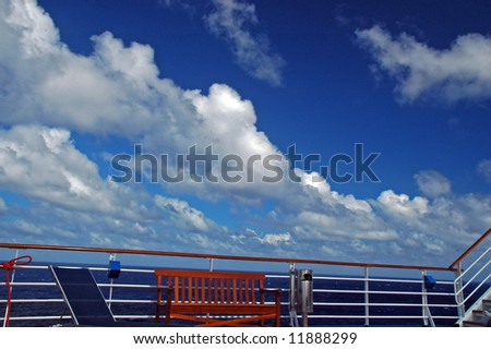 View of a Cruise Ship Railing, Stairs and Bench with beautiful Tropical Sky in the background - stock photo