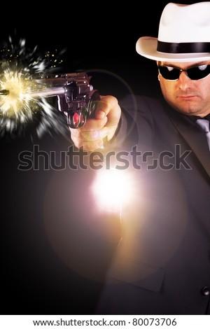 View of a dark suit gangster man firing a gun. - stock photo