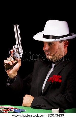 View of a dark suit gangster man holding a gun.