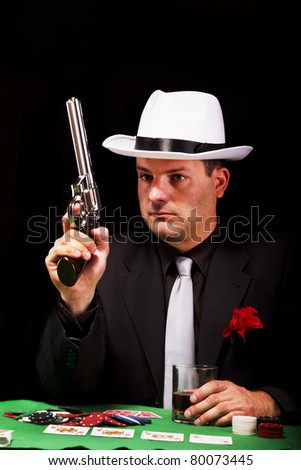 View of a dark suit gangster man holding a gun. - stock photo