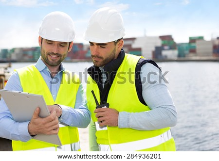 View of a Dock worker and supervisor checking containers data