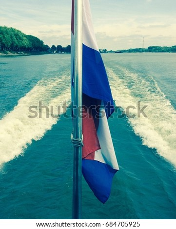 View of a Dutch flag flying from the back of a river bus on the Beneden Merwede