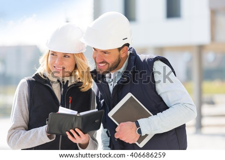 View of a Engineer and architect dating next appointment on a construction site