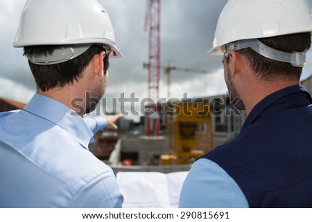 View of a Engineer and worker checking plan on construction site  - stock photo