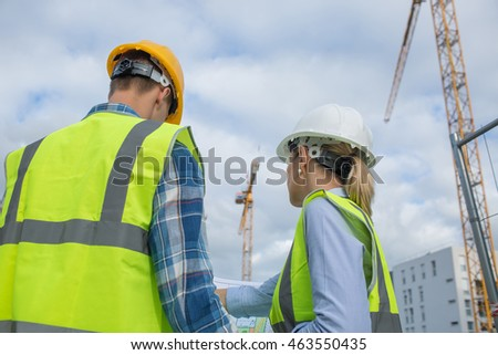 View of a Engineer and worker checking plan on construction site
