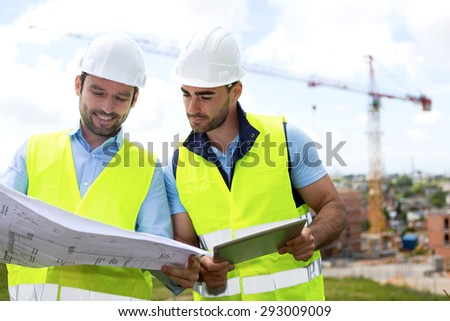 View of a Engineer and worker watching blueprint on construction site