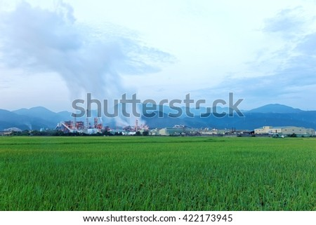 View of a factory in the middle of a green farmland in the early morning  ~ Factory pipes polluting air in a silent morning, a serious environmental issue - stock photo