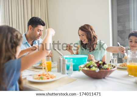 View of a family of four sitting at dining table in the home - stock photo