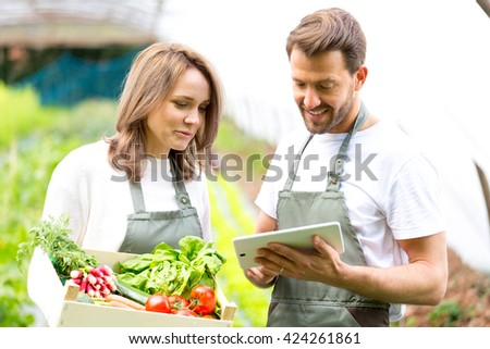 View of a Farmers working on a tablet after collecting vegetables - stock photo