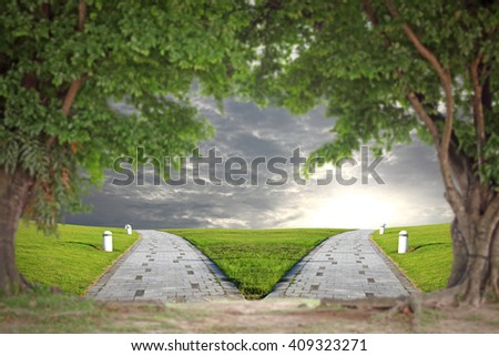 View of a fork road leading to sunrise and nightfall through the opening of a green tropical trees. - stock photo