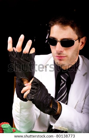 View of a gangster man playing some cards and poker, adjusting the gloves. - stock photo