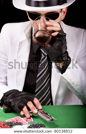 View of a gangster man playing some cards and poker, having a drink. - stock photo