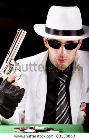 View of a gangster man playing some cards and poker, holding a gun. - stock photo