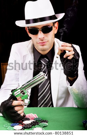 View of a gangster man playing some cards and poker, smoking a Cuban cigar. - stock photo