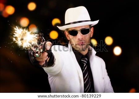 View of a gangster man with a scar, firing a gun, we can see the bullet. - stock photo