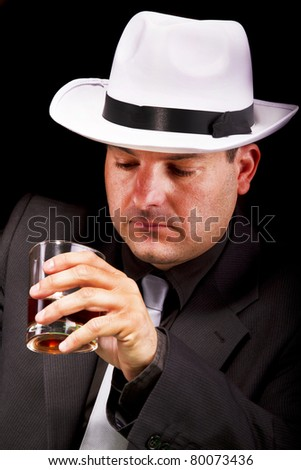 View of a gangster man with white hat drinking some liquor. - stock photo