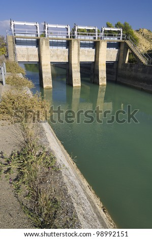 view of a gate in an irrigation canal - stock photo