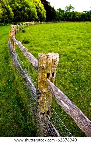 View of a green colourful field with wooden fence running through the middle with trees in the background - stock photo