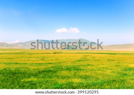 View of a green field, blue sky and hills in the distance. Toned