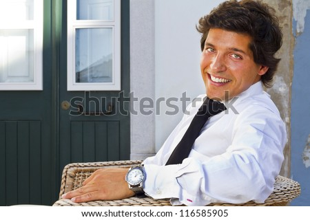 View of a happy business man with a black suitcase on a European city. - stock photo