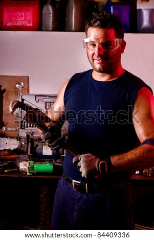 View of a happy garage mechanic man holding an adjustable spanner.