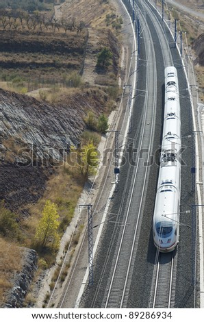 view of a high-speed train crossing a arid landscape in Purroy, Saragossa, Aragon, Spain; AVE Madrid Barcelona - stock photo