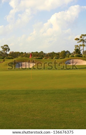 View of a landscaped golf course with flag and sand traps with cloudy sky. Vertical shot.
