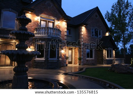 view of a large luxurious home in the evening after a light rain with a fountain in the front - stock photo