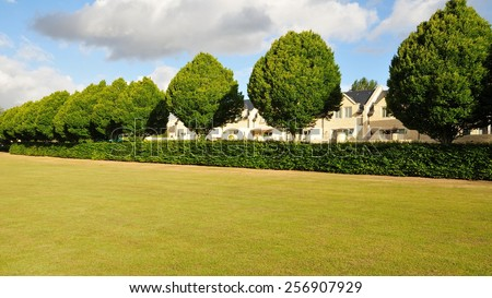 View of a Lawn in a Landscaped City Park with a Line of Trees and Hedgerow - stock photo