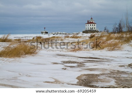 View of a lighthouse on Lake Erie from the snow covered dunes - stock photo