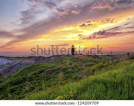 View of a lighthouse with colorful sky n the background. - stock photo